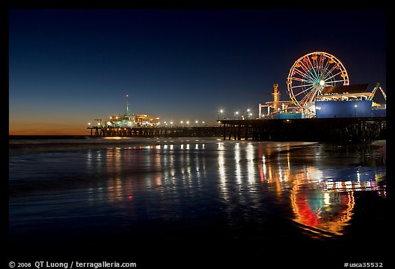 Ferris Wheel and pier reflected on wet sand at night. Santa Monica, Los Angeles, California, USA