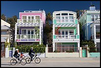 Family cycling in front of colorful beach houses. Santa Monica, Los Angeles, California, USA (color)