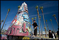Man painting inscriptions on a graffiti-decorated tower. Venice, Los Angeles, California, USA (color)