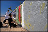 Young men creating graffiti art on a wall on the beach. Venice, Los Angeles, California, USA