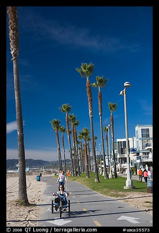 Woman riding a tricycle on the beach promenade. Venice, Los Angeles, California, USA (color)