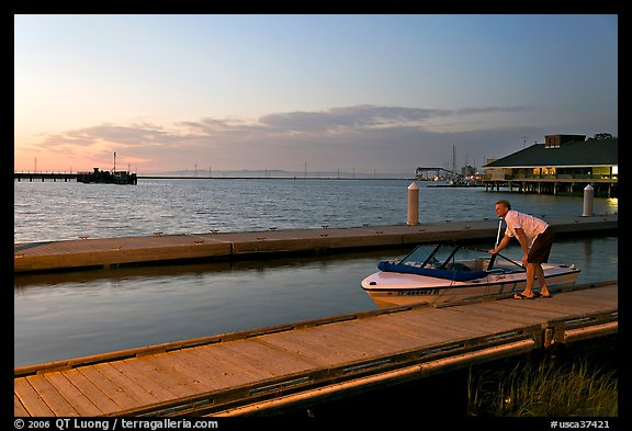 Man holding small boat, Redwood marina, sunset. Redwood City,  California, USA (color)