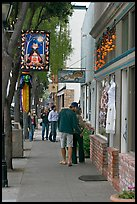 People looking at store display on Main Street. Half Moon Bay, California, USA (color)