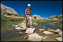 Woman crossing stream on rocks, John Muir Wilderness. California, USA