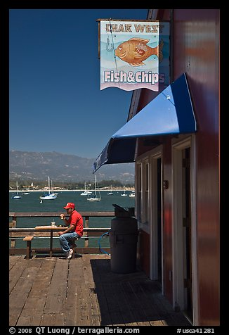 Man eating on wharf next to Fish and Chips restaurant. Santa Barbara, California, USA (color)