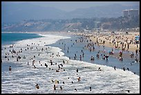 Many people bathing in surf at Santa Monica Beach. Santa Monica, Los Angeles, California, USA