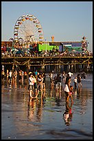 Pier and beachgoers reflected in wet sand, late afternoon. Santa Monica, Los Angeles, California, USA