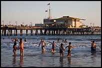 People bathing in ocean and Santa Monica Pier, late afternoon. Santa Monica, Los Angeles, California, USA (color)