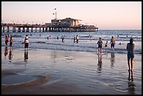 Beachgoers near Santa Monica Pier reflected in wet sand, sunset. Santa Monica, Los Angeles, California, USA