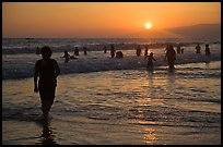 Ocean bathers at sunset, Santa Monica Beach. Santa Monica, Los Angeles, California, USA