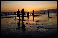 People and reflections on beach at sunset, Santa Monica Beach. Santa Monica, Los Angeles, California, USA
