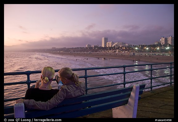 Two women sitting on bench at sunset , Santa Monica Pier. Santa Monica, Los Angeles, California, USA (color)