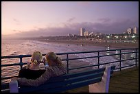 Two women sitting on bench at sunset , Santa Monica Pier. Santa Monica, Los Angeles, California, USA ( color)
