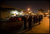 People lining up to enter a gallery at night, Bergamot Station. Santa Monica, Los Angeles, California, USA (color)