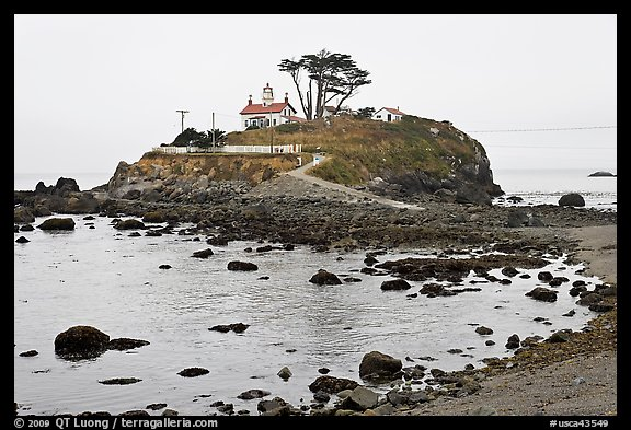 Rocky mound and lighthouse, Crescent City. California, USA (color)