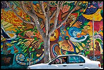 Man sitting in car, mural, and tree, Mission District. San Francisco, California, USA ( color)