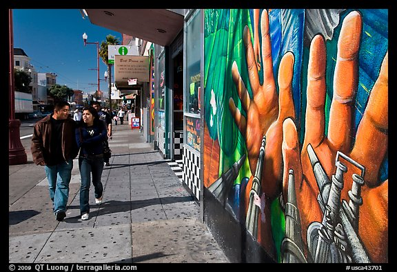 Couple walks past mural on Mission street, Mission District. San Francisco, California, USA (color)