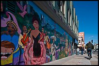 Man riding bicycle on sidewalk past mural, Mission District. San Francisco, California, USA (color)