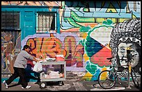 Man pushes vending cart pass mural and bicycle, Mission District. San Francisco, California, USA ( color)
