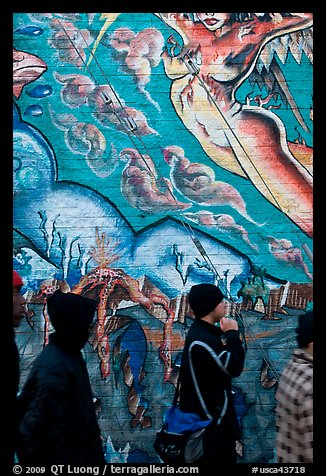 Men in dark jackets walk past mural, Mission District. San Francisco, California, USA (color)