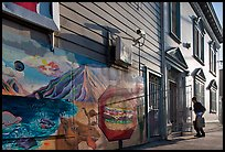 Mural and man entering house with grocery bags, Mission District. San Francisco, California, USA (color)