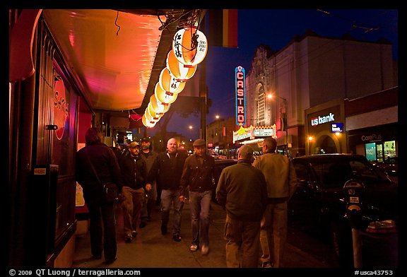 Men walking on sidewalk, Castro street at night. San Francisco, California, USA (color)