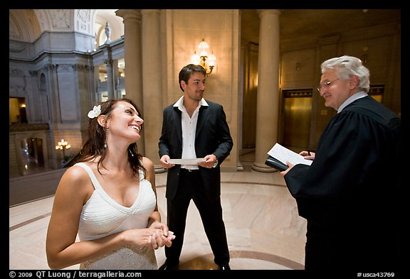 Bride and groom exchange smile with wedding official, City Hall. San Francisco, California, USA (color)