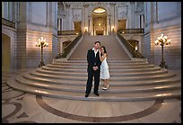 Just married couple at the base of the grand staircase, City Hall. San Francisco, California, USA (color)