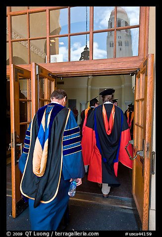 Professors in academic regalia walk into door with Hoover tower reflected. Stanford University, California, USA (color)