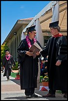 Graduate wearing lei presented with diploma. Stanford University, California, USA