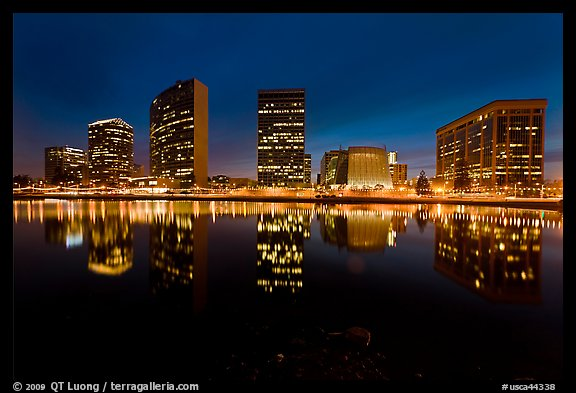 High-rise buildings and Oakland Cathedral reflected in Lake Meritt at night. Oakland, California, USA (color)