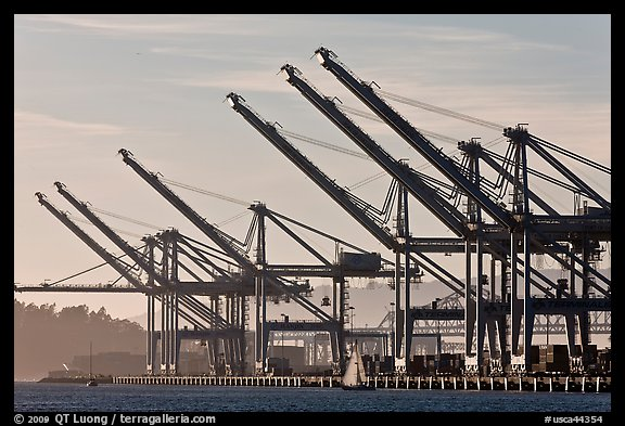 Giant cranes dwarf yacht Port of Oakland. Oakland, California, USA (color)