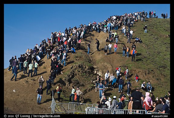 Crowds scrambling on hill during mavericks competition. Half Moon Bay, California, USA (color)