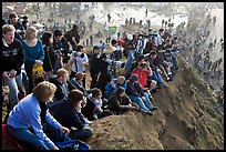 Spectators sitting on cliff to see mavericks contest. Half Moon Bay, California, USA (color)
