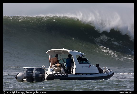 Small boat dwarfed by huge wave. Half Moon Bay, California, USA (color)
