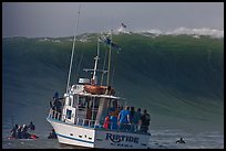 Judging boat with huge wave and surfer at crest. Half Moon Bay, California, USA