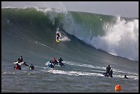 Surfer down huge wall of water observed from jet skis. Half Moon Bay, California, USA