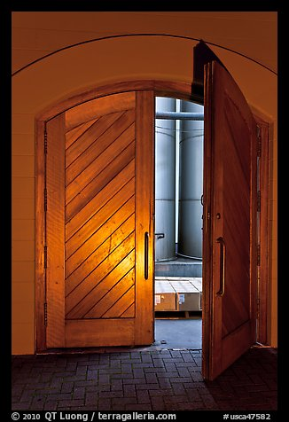 Wooden door opening to wine storage tanks. Napa Valley, California, USA