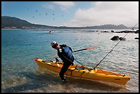 Man boards sea kayak, Carmel Bay. Carmel-by-the-Sea, California, USA (color)