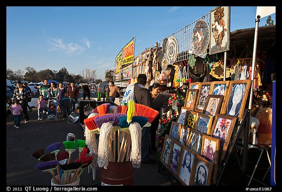 Brooms and religious pictures for sale, San Jose Flee Market. San Jose, California, USA (color)