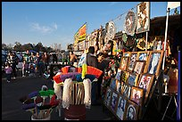 Brooms and religious pictures for sale, San Jose Flee Market. San Jose, California, USA