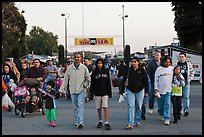 Families walking with entrance sign behind, San Jose Flee Market. San Jose, California, USA (color)