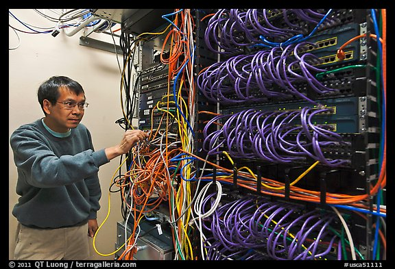 Technician rearranging data cables. Menlo Park,  California, USA (color)