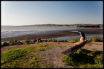 Woman sitting on bench, Carquinez Strait Regional Shoreline. Martinez, California, USA (color)
