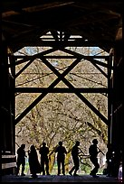 Silhouettes of people dancing inside covered bridge, Felton. California, USA (color)