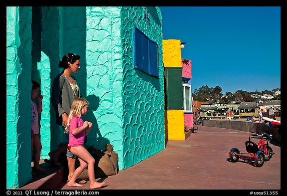 Family steps out of colorful cottage. Capitola, California, USA (color)