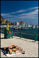 Women sunning on beach near harbor, Avalon, Catalina. California, USA (color)