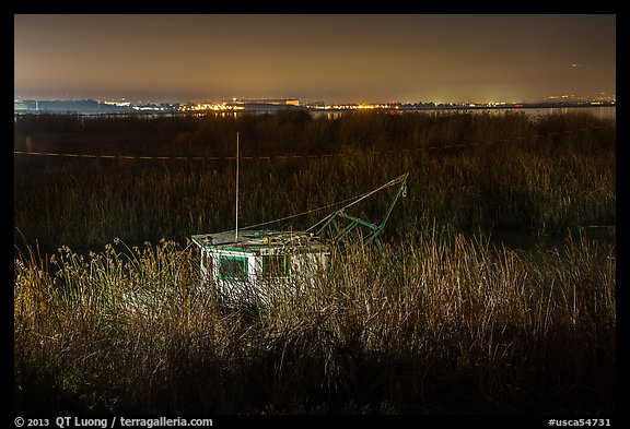 Fishing boat amongst tall grasses by night, Alviso. San Jose, California, USA (color)