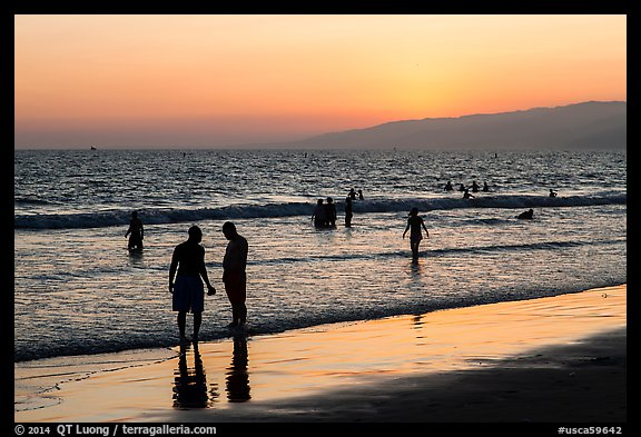 Sunset with beachgoers in water. Santa Monica, Los Angeles, California, USA (color)