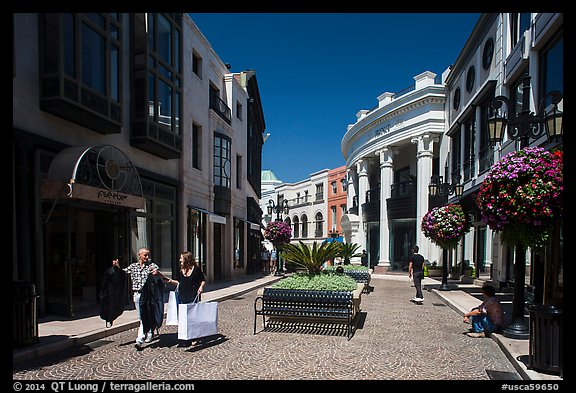 People carry garnments in  Rodeo Drive shopping district. Beverly Hills, Los Angeles, California, USA (color)